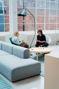 two people sitting and conversing in an open bright space